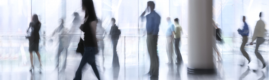 abstract image of a business people rushing in the lobby in intentional motion blur and a blue tint,some of them using mobile phones